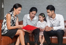 Asian Parent talking with teacher about Plan education for children. Young family and children discuss or advice with professional family psychologist in office