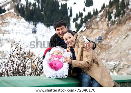 Asian parents with their baby in mountains in winter time