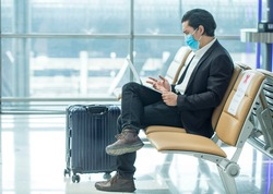 Asian passenger businessman wear masks covid19 disease prevention and Teleconference with laptop while traveling to work abroad at the airport terminal.New normal and Business trip concept