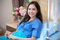 Asian Patient woman sick saline intake in hospital. Beautiful lady with patient dress, smile get well sitting on patient's bed in hospital. Saline bottle hanging, Flower vase are at room