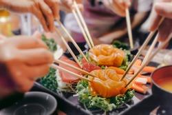 Asian people eating sashimi set in Asian restaurant