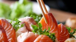 Asian people eating sashimi set in Asian restaurant. Hirame sashimi,salmon sashimi and tuna sashimi dish. Japanese food concept.