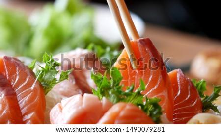 Asian people eating sashimi set in Asian restaurant. Hirame sashimi,salmon sashimi and tuna sashimi dish. Japanese food concept. Foto d'archivio ©