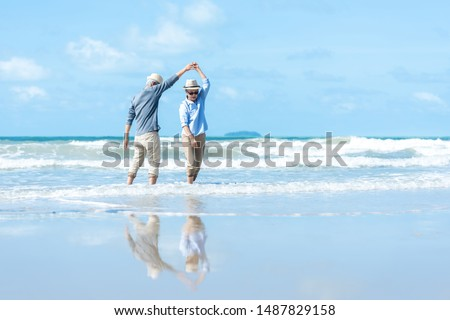 Asian people older senior elderly dancing on the beach happy and relax time.Tourism couple family travel leisure and activity after retirement in vacations and summer. Beach Background