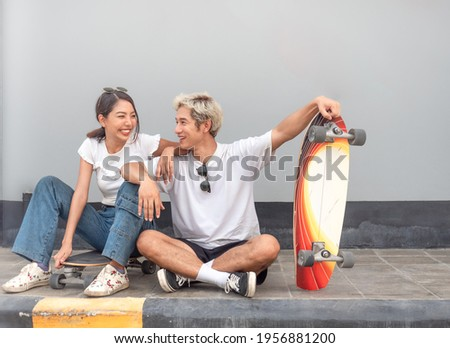 Asian people skateboarder couple sitting together on pavement relaxing after exercise. Happy woman sits on a surf skateboard laughing while a man smile. Trendy outdoor recreation sport in Thailand. Stock photo ©