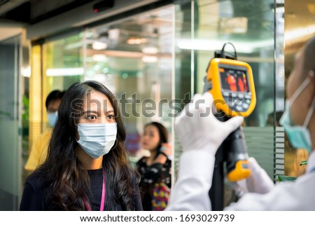 Asian people waiting for body temperature check before access to building for against epidemic flu covid19 or corona virus from wuhan in office by thermoscan or infrared thermal camera