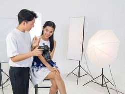 Asian photographers allow models to view pictures taken on the camera screen. The young model is very satisfied with her photo.
