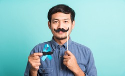 Asian portrait happy handsome man posing he holding a light blue ribbon and mustache, studio shot isolated on blue background, Prostate Cancer Awareness in November concept