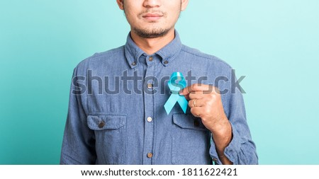Asian portrait happy handsome man posing he holding light blue ribbon for supporting people living and illness, studio shot isolated on blue background, Prostate Cancer Awareness concept