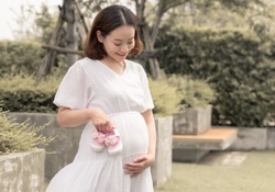 Asian pregnant beautiful mother holding pink girl's shoes while standing in garden