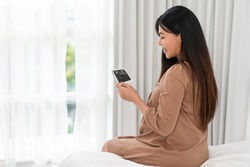 Asian pregnant woman in brown dress holding ultrasound on her belly in bed at bedroom. Pregnancy, parenthood, preparation and expectation concept