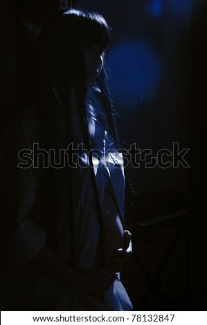 stock photo : asian pregnant woman in the dark room