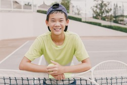 Asian preteen tween boy playing tennis,  healthy young teen athletes training, active well being concept