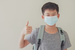 Asian preteen tween teen boy student wearing mask and giving thumb up, school reopening, ready to return back to school after covid-19 delta pandemic is over, new normal concept
