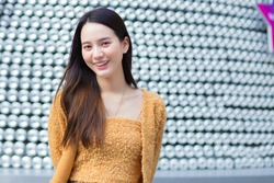 Asian pretty woman in long hair wears a yellow sweater and brightly smiles in Valentine's theme. abstract background