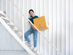 Asian pretty young girl carrying heavy cardboard alone to upstairs white ladder with smiling face and casual style for manage stuff and furniture after relocation and moving to new modern apartment