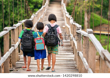Asian primary school girls in casual clothes walking cross a simple suspension footbridge at dusk, rural scene near Thailand and Myanmar border. Education concept.