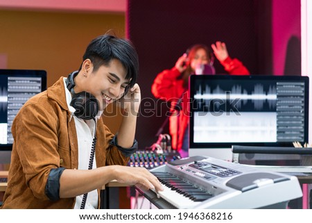 Asian producer standing by sound mixing console. Happy male music composer artist with a woman singer background   ストックフォト ©