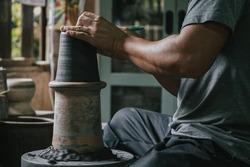Asian professional artisan potter making art pot or vase handicraft on wheel in pottery workshop studio.