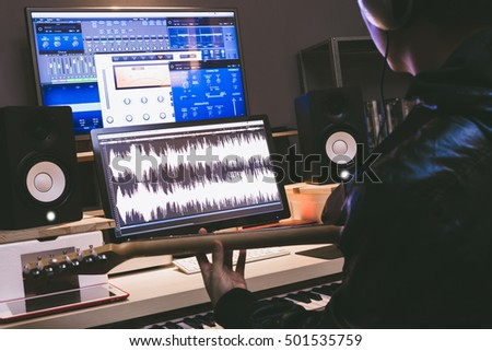 asian professional musician recording electric guitar in digital studio, music production technology concept