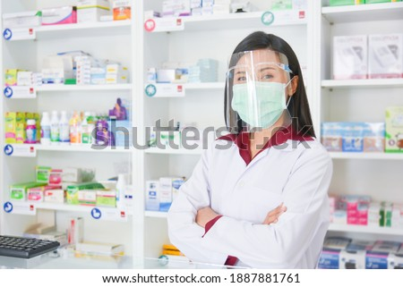 Asian professional young pharmacist wearing faceshield and mask while standing at drugstore.