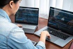 Asian programmer woman looking on multiple laptop screen and holding pen pointing while working to writing coding database and development website or applications in software development office