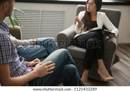 Asian psychologist counseling talking to unhappy couple in office, family counselor sexologist sitting in chair consulting family during therapy session, marriage and sexual problems solution concept