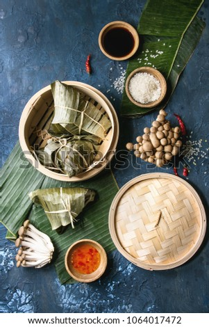 Asian rice piramidal steamed dumplings from rice tapioca flour with meat filling in banana leaves served in bamboo steamer. Ingredients and sauces above over blue texture background. Top view, space. Zdjęcia stock ©