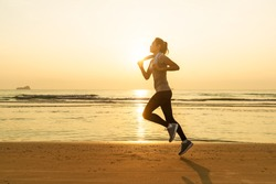 Asian runner good shape woman running on beach in sunset light with wave and sun in background. Concept in workout for good health and heathcare of modern people.