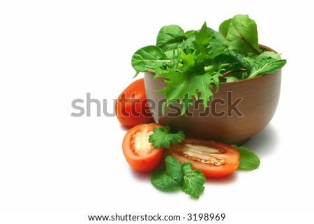 Asian salad greens (baby leaves) in timber bowl, cut and whole roma tomatoes, isolated on white