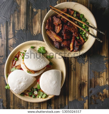 Asian sandwich steamed gua bao buns with pork belly, greens and vegetables served in ceramic plate over dark wooden plank background. Asian style fast food dinner. Flat lay. Square image