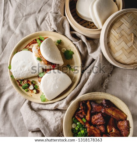 Asian sandwich steamed gua bao buns with pork belly, greens and vegetables served in ceramic plate over linen tablecloth. Asian style fast food dinner. Flat lay, space. Square image