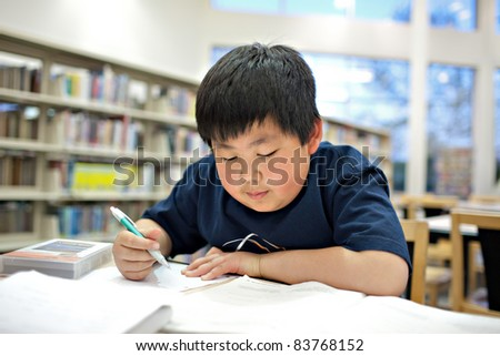 Asian School Boy Working on Homework at Library, Shallow DOF