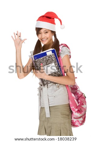 Asian school girl wearing red Santa Claus hat with backpack holding Composition book, notebooks and pen waives her hand making greeting gesture - stock photo