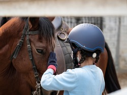 Asian school kid learning or practising to horse ridding.Girl wearing mask while practicing.
