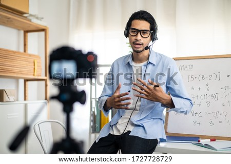 Asian school male teacher working from home teaching online math subject to student studying from home. Man using camera to record his live in internet. Remote education class during covid19 pandemic.