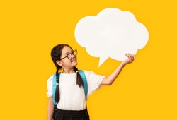 Asian Schoolgirl Holding Blank Speech Bubble Posing Over Yellow Studio Background. Mockup, Free Space