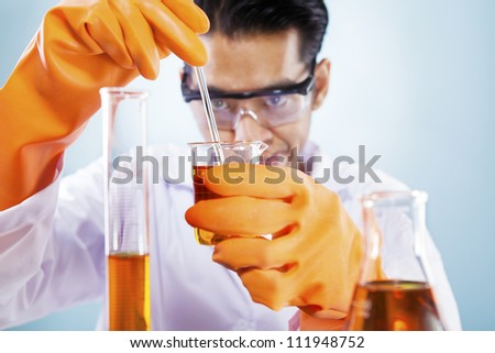 Asian scientist mixing chemicals shot in studio against blue background