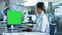 Asian Scientist Sitting at His Desk Works on a Personal Computer with Mock-up Green Screen. In the Background Computer Science Research Laboratory with Robotic Arm Model.