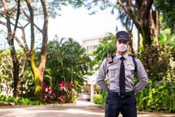 Asian security guard make saluting entry entrance the village. Security Guard Talking a portable wireless transceiver guard entrance to the village door. Speed 15 limit in area, copy space.