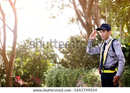 Asian security guard make saluting entry entrance the village. Security Guard Talking a portable wireless transceiver guard entrance to the village door. Speed 15 limit in area,copy space.