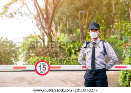 Asian security guard make saluting entry entrance the village. Security Guard with mask, protect covid-19 warning. Guard check entrance to the village. Speed 15 limit in area, copy space.
