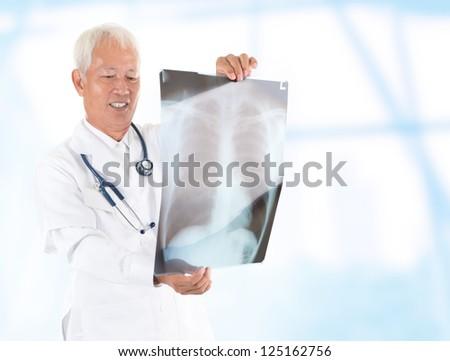 Asian senior doctor checking on x-ray image inside hospital room
