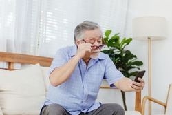 Asian senior fatigue man taking off eye glasses during using smartphone after surfing internet or social media at home. Elderly retired male eyesight problem or blurry vision from old aged