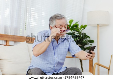 Asian senior fatigue man taking off eye glasses during using smartphone after surfing internet or social media at home. Elderly retired male eyesight problem or blurry vision from old aged Foto stock ©