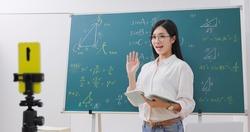 asian senior high school female teacher teach math online through mobile phone in classroom