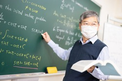 asian senior male calculus professor wearing face mask  is writing on blackboard in the classroom at college