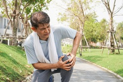 Asian senior man falling down and getting knee hurt from walking or jogging exercise at the park. pain and injury for elderly insurance concept.
