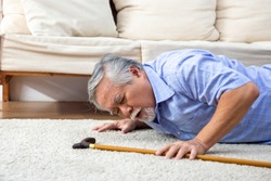 Asian senior man falling down on carpet and lying on the floor in living room at home, Falls of older adults concept