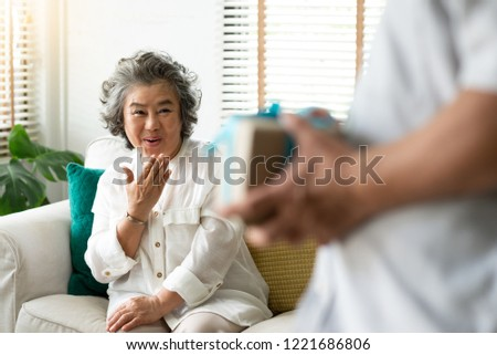 Asian Senior man holding gift or present box while his wife smiling and looking to him. Making a surprise for Christmas, birthday and New year concepts.